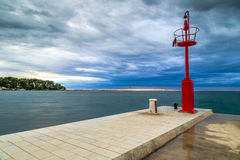 Sunset on docks. On the Mediterranean sea with red steel look-out post and white lighthouse in the cloudy background near Porec in Croatia Royalty Free Stock Photos
