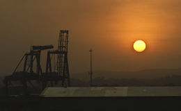 Sunset at the Docks, Panama. The sun sets at the port of Colon, Panama, on the Atlantic Ocean side of the Panama Canal, with a crane silhouetted against the Royalty Free Stock Images