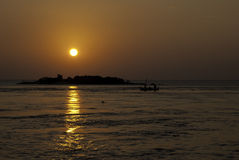 Sunset with Dolphin at Maldives. A silhoutte sunset shot of a maldivian island with a traditional boat and dolphins in front Stock Images