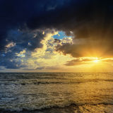 Sunset in dramatic clouds over dark sea Stock Photo
