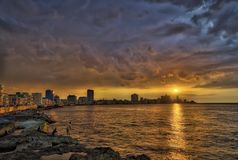 Sunset and dramatic clouds over Havana skyline with fishermen in foreground. Great travel photo of beautiful sunset at the Malecon, Havana`s harbor, and Havana Stock Images