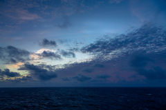 Sunset and dramatic set of clouds drifting over the tropical waters of the Caribbean Sea are lit by the last moments of daylight. Stock Photos