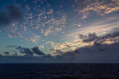 Sunset and dramatic set of clouds drifting over the tropical waters of the Caribbean Sea are lit by the last moments of daylight. Royalty Free Stock Photo