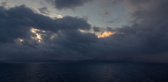 Sunset and dramatic set of clouds drifting over the tropical waters of the Caribbean Sea are lit by the last moments of daylight. Royalty Free Stock Photos