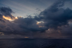Sunset and dramatic set of clouds drifting over the tropical waters of the Caribbean Sea are lit by the last moments of daylight. Royalty Free Stock Images