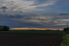 Sunset with a dramatic sky over the agricultural fields in Vroenhoven stock photo