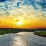 Sunset in dramatic sky over river Royalty Free Stock Photo