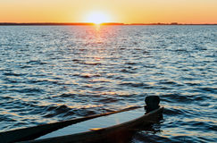 Sunset and drowned boat on summer lake bank. Sunset and old drowned wooden fishing boat on summer lake bank Stock Photos