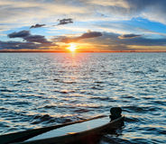 Sunset and drowned boat on summer lake bank Stock Image