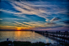Sunset from Dunedin Park, FL. Rainbow colors layer the sky over Florida`s Gulf at sunset. A wooden pier off Weaver Park runs obliquely toward the setting sun Royalty Free Stock Images