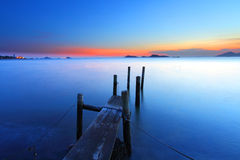 Sunset at dusk along a wooden pier Royalty Free Stock Image