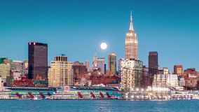 Sunset, dusk and night with a Super Moon rising above New York skyline stock video footage