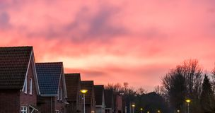 Sunset in a dutch neighborhood, pink nacreous clouds in the sky, a rare weather phenomenon royalty free stock images