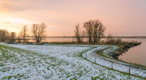 Sunset at a Dutch river. In the winter seaon. Bare trees contrast against the orange and pink sky. There is still some snow Stock Photos
