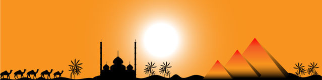Sunset in Egypt, panorama. Sunset in Egypt with mosque, pyramids and camels, panorama Royalty Free Stock Photography