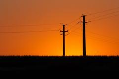 Sunset and electric pylons Stock Photos