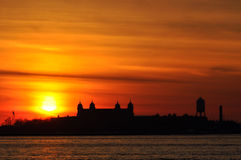 Sunset on Ellis Island in NYC bay. Sunset in New York City with silhouette of Ellis Island stock photography