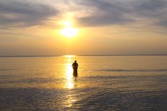 The Sunset Embraces the Man. This pristine sunset captivated this lone man and beckoned him to walk into the lake and know this special scene. He quietly stood stock image