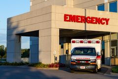 Sunset At The Emergency Room. An ambulance parked at a hospital emergency room at sunset stock photos