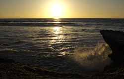 Sunset Errosion. Waves splashing upon a rocky shore in san diego Royalty Free Stock Image