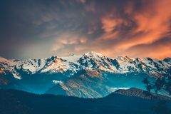 Sunset evening view over the snowy mountain range. Beautiful colorful sunset over the snowy mountain range and pine tree forest. Nature landscape. Dramatic Stock Images