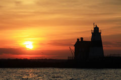 Sunset and Execution Rocks Lighthouse. Execution Rocks Lighthouse with a bright orange sunset Royalty Free Stock Images