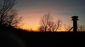 Sunset in fall. Pink t ellow blue orange sunset tree otlune royalty free stock photography