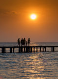Sunset family. Silhouette of family walking over a bridge at sunset Royalty Free Stock Photo