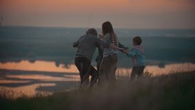 At sunset, the family hold hands, have fun dancing and spinning