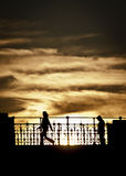Sunset farewell. Two silhouettes and dramatic clouds Royalty Free Stock Photos
