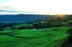 Sunset on the farm. The sun disappearing over the mountain Stock Image