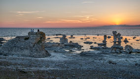Sunset at Faro island. Faro, Sweden – June 8, 2014: Tourists sitting on a sea stack enjoy the sunset at Faro island in the Baltic sea. Faro is famous for royalty free stock photography