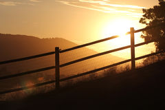 Sunset through a fence. The sun sets behind a lodge pole fence with a silhouette of mountains, trees, and grass Royalty Free Stock Photos