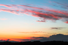 Sunset. On a field with colorful clouds Royalty Free Stock Photography