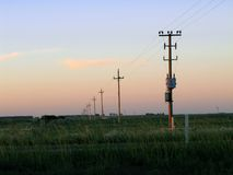 Sunset in the field. A sunset in the countryside where the electric poles continue to the horizon, Salto, Uruguay, South America Royalty Free Stock Photo