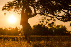 Sunset in the field of freedom she enjoys. Young girl enjoying the freedom of the wild stock photography