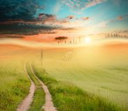 Sunset field and road. Photo of field with fresh green grass, setting sun and road; green, orange and blue colors Stock Photo