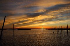 Sunset on fire. The Sunset was bright vibrant and colorful. The clouds were multicolored and the reflection on the water was stunning. The old pilings in the royalty free stock photo