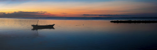 Sunset with fisher boat and still water on Gili Air Island, Indo Stock Photos
