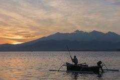 Sunset with fisher man fishing in a boat in ocean near Gili Air Royalty Free Stock Images