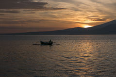 Sunset with fisher man fishing in a boat in ocean near Gili Air Royalty Free Stock Image