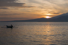 Sunset with fisher man fishing in a boat in ocean near Gili Air Stock Images