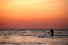 Sunset fisherman. Fisherman in the sean on vivid orange sunset. Sochi, Russia stock image
