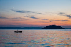 Sunset, fisherman  on his boat Royalty Free Stock Photo