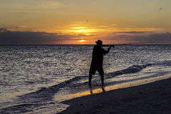 Sunset Fisherman. Silhouette of a fisherman casting a fishing rod at sunset on Sanibel Island Florida stock images