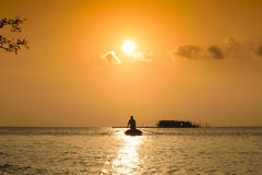 Sunset and fisherman silhouette. Natural gold sunset and fisherman at the sea Royalty Free Stock Image