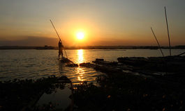 Sunset. Fishermen return by using a raft in a lake as the sun began to sink in Boyolali, Central Java, Indonesia Royalty Free Stock Photos