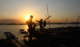 Sunset. Fishermen return by using a raft in a lake as the sun began to sink in Boyolali, Central Java, Indonesia Stock Images