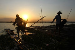 Sunset. Fishermen return by using a raft in a lake as the sun began to sink in Boyolali, Central Java, Indonesia Stock Image