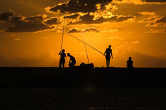 Sunset Fishing. Fishermen silhouette and dramatic golden sky Royalty Free Stock Photos